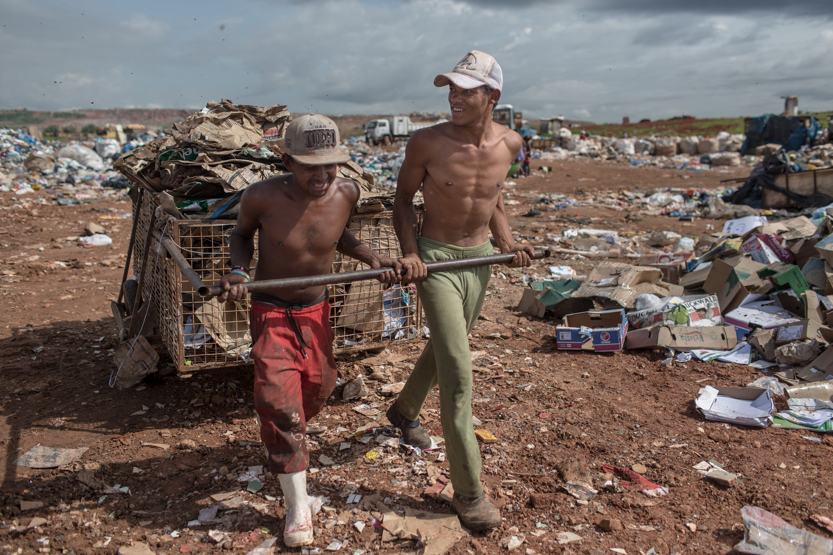José Hilton dos Santos Souza, 20, right, and his friend, Cleiton de Jesus, 29, left, carrying cardboards at the Estrutural dump in Brasilia, on Monday, Jan. 15, 2018. They know each other since they began working at the dump when they were kids.