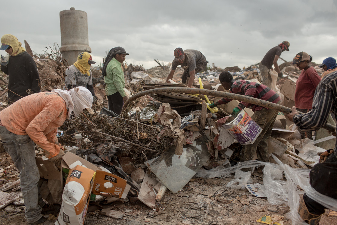A group of trash pickers look for paper, copper, plastic, beer cans and whatever else they can sell to middlemen, who then transport the items to a local recycling center, at the Estrutural dump in Brasilia, on Monday, Jan. 15, 2018.