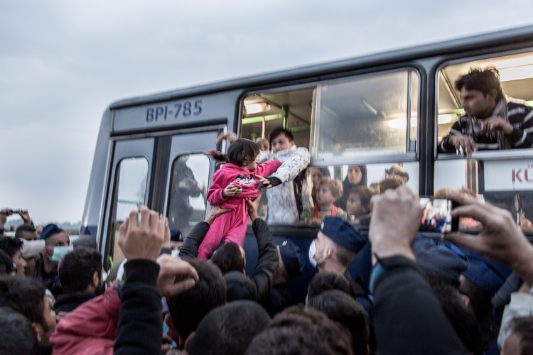 "A child is passed through the bus window after being separated from her family when entering the bus to a ""registration camp"" at Roszke, Hungary."
