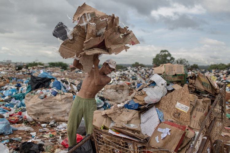 José Hilton dos Santos Souza, 20, throws cardboard and papers into a pile at the Estrutural dump in Brasilia, on Monday, Jan. 15, 2018. José said he can earn around 120 to 155 USD per week working at the largest dump in Latin America. . The largest waste dump in Latin America is shutting down in Brasilia for sanitary reasons, upending the livelihood of thousands of garbage recyclers.