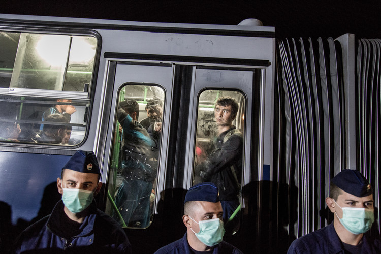 "Man looks out the bus window while being taken away to a ""registration camp"" in Roszke, Hungary."