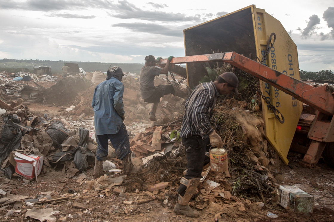 Recyclers helps to unload a container at the Estrutural dump in Brasilia, on Monday, Jan. 15, 2018. The conditions in some areas of the dump can be very dangerous. Falling containers or getting runned over by trucks are common accidents in Estrutural dump.