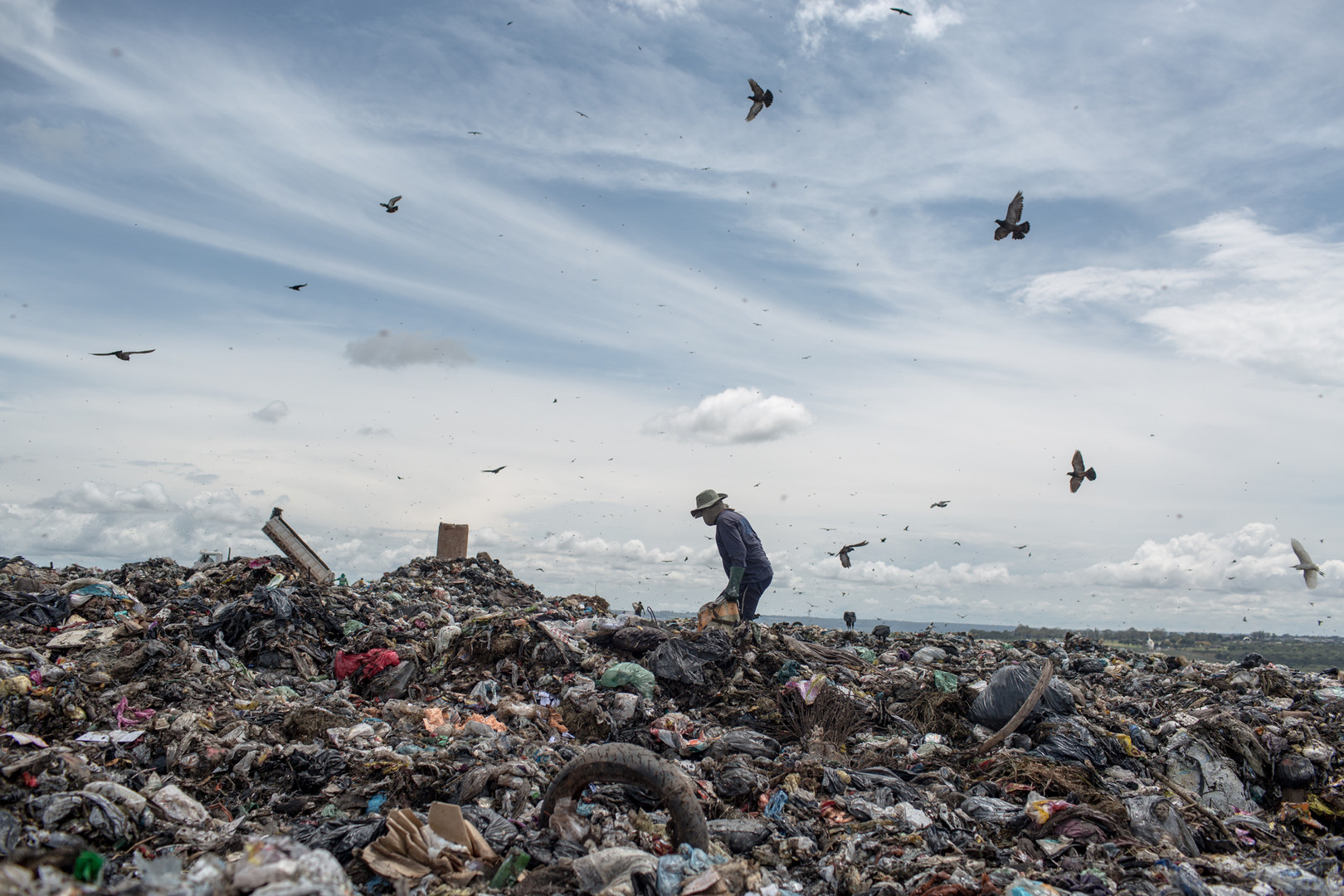 A picker walks through a pile of wet waste at the Estrutural dump, in Brasilia, on Monday, Jan. 15, 2018.