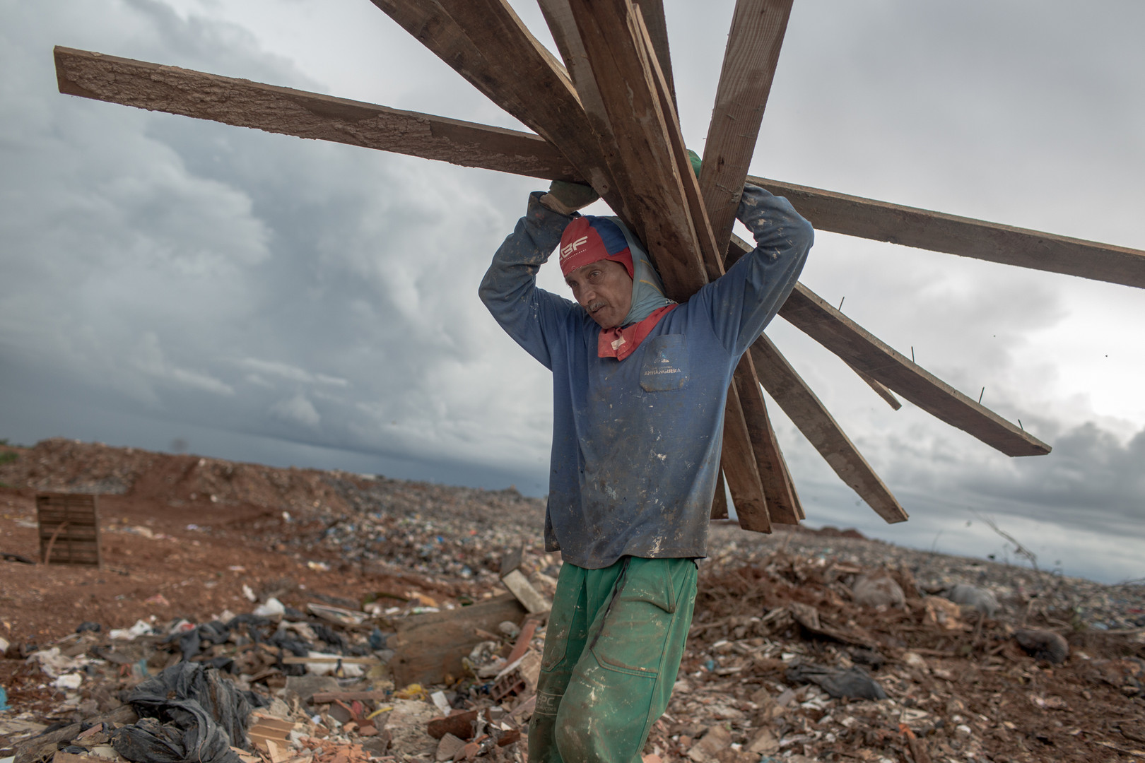 A recycler brings wood to his pile of trash picked at the Estrutural dump in Brasilia, on Monday, Jan. 15, 2018. The trash pickers look for paper, copper, plastic, beer cans and whatever else they can sell to middlemen, who then transport the items to a local recycling center. . Estrutural, the largest waste dump in Latin America is shutting down in Brasilia for sanitary reasons, upending the livelihood of thousands of garbage recyclers.