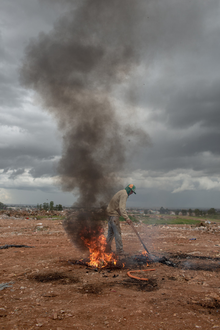 Jailson de Souza Matos, 31, burns a pile of wires to collect the copper at the Estrutural dump in Brasilia, on Monday, Jan. 15, 2018. Mr. Matos, who has five children, began working at the dump in 2012, when he lost his construction job.