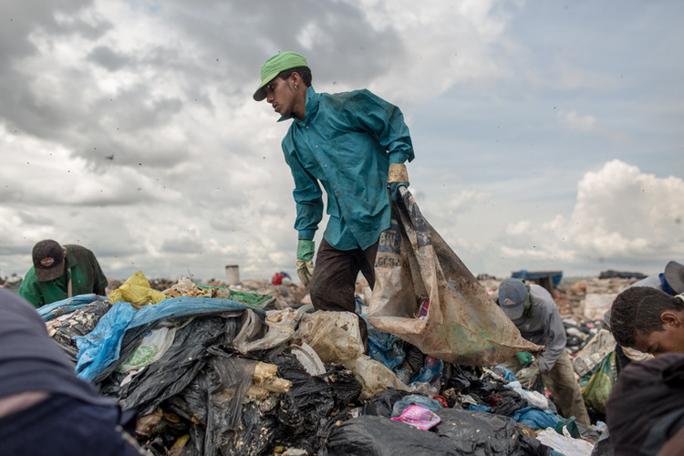A picker walks through a pile of wet waste at the Estrutural dump, in Brasilia, on Monday, Jan. 15, 2018. The dump holds around 40 million tons of trash accumulated over the years in the 500-acre area. Some 2,000 tons of waste are dumped there every day.