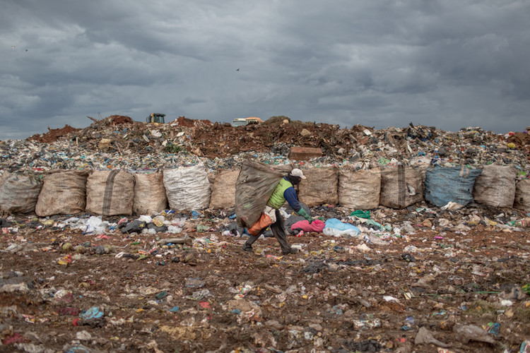 A recycler carries a load of trash picked from the wet waste sector at the Estrutural dump in Brasilia, the largest waste dump of Latin America. . The dump is shutting down in Brasilia for sanitary reasons, upending the livelihood of thousands of garbage recyclers.