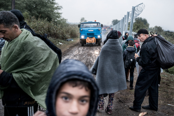 Refugees crossing the border with the fence still unfinished.