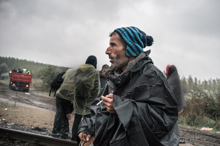 Men smokes a cigarette and rests before he crosses the border to the Hungary side. Many doubts and hesitation.