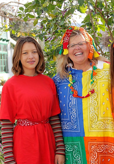 A girl in a red dress smiles next to a woman in a dress made from bandanas in bright blue, yellow, green, and orange.