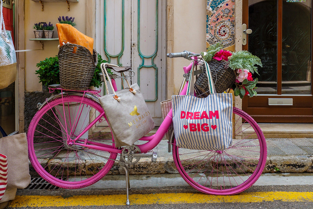 Colourful pink bike with flowers and reusable tote bag in a pretty street