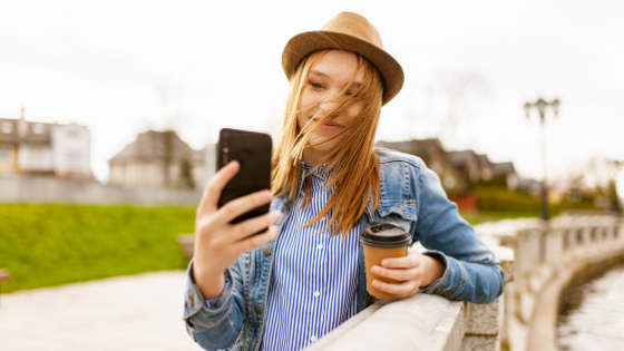 influencer taking a selfie with a coffee on a scenic overlook
