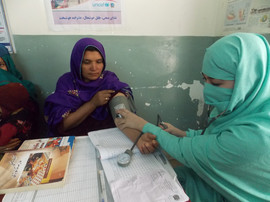 Behsood Health Clinic staff checking blood pressure for mother
