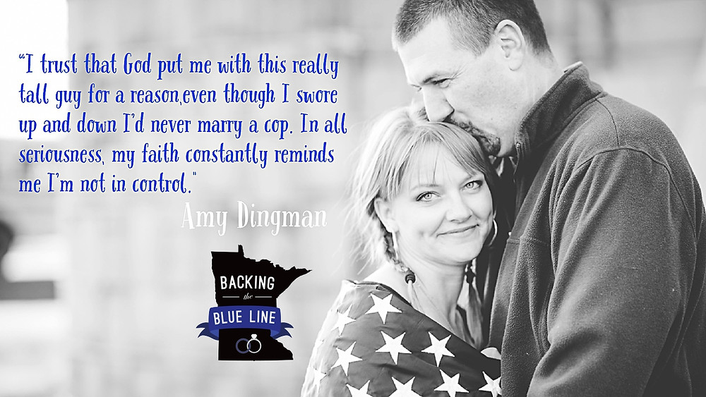 Black and white photo of a smiling police wife wrapped up in a police flag and her husband's arm.  He is kissing the top of her head and she is looking straight at the camera.  A quote from her is included along with the Backing the Blue Line Logo. Photo by jamiecramble.com.