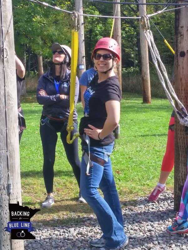 Photos of a smiling police wife wearing a red helmet and safety lines waiting for her turn to go on a ropes course up in the trees at a weekend retreat.