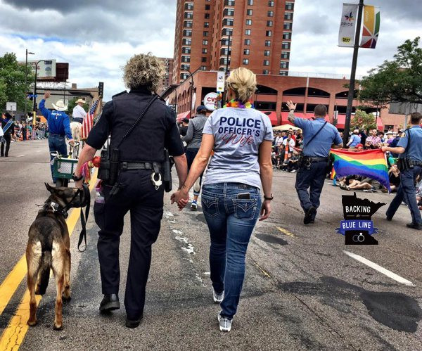 Photo of female police officer, her dog and her same sex wife marching in the street during the Minneapolis Pride parade