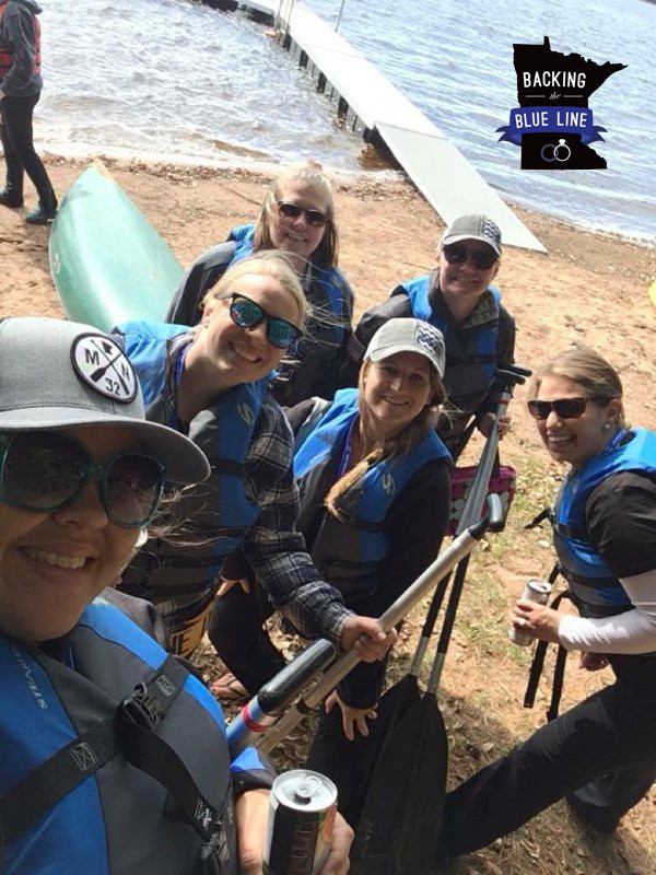 A group of six police wives getting ready to canoe on the lake