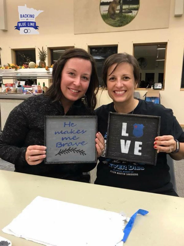 Two brown haired police wives holding up their handprinted wooden signs they made during craft night at SWAT 2017