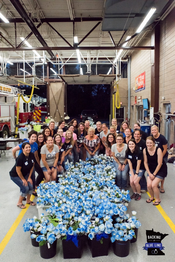 Photo of 28 MN police wives standing behind 2,000 blue roses that were prepared for the funeral of Officer Mathews in Septermber 2017 after being killed in the line of duty.
