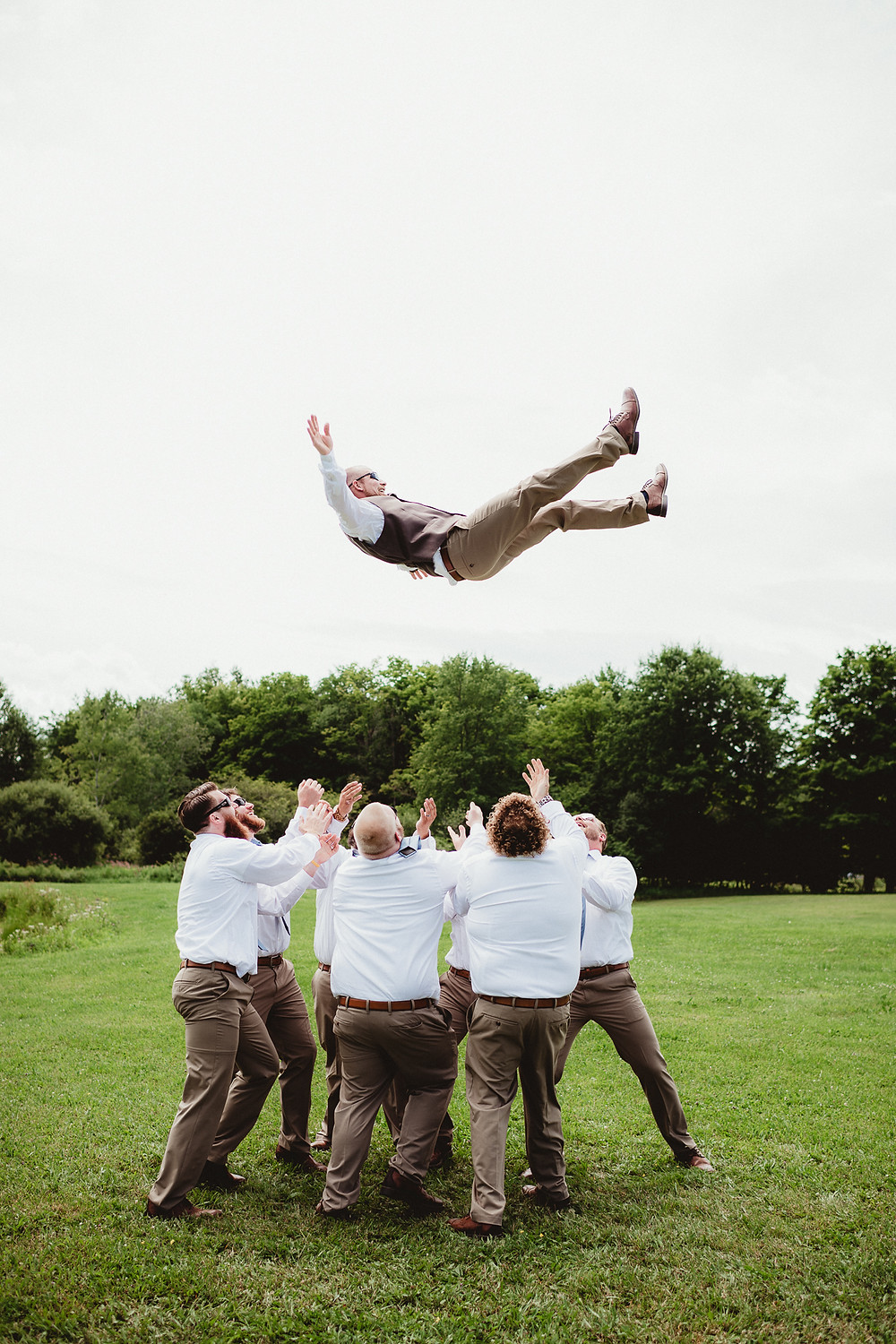 Groom being tossed in the air by groomsmen before his wedding. Rochester, NY photography.