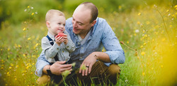 Father holding son in apple field