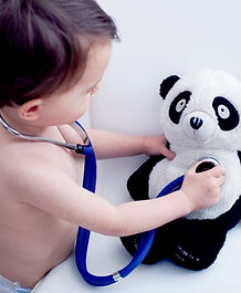 Toddler with toy panda and stethoscope