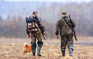 Men and ther dogs walking in camouflage shooting gear
