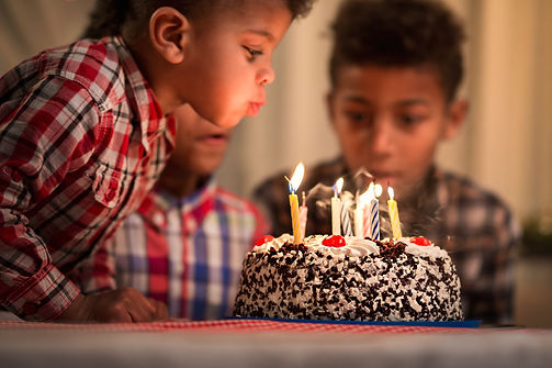 Black toddler blowing candles out. Child