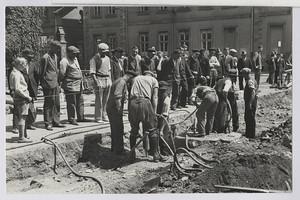 01.05 Arbeitslose Zuschauer beim Straßenbau vor dem Arbeitsamt