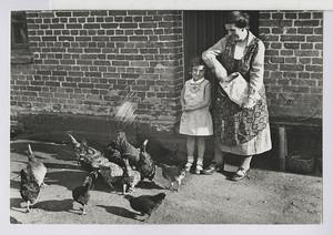 11.04 Frau und Kind im Sonntagsstaat (füttert Hühner)