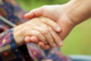 Doctor's hand holding a wrinkled elderly