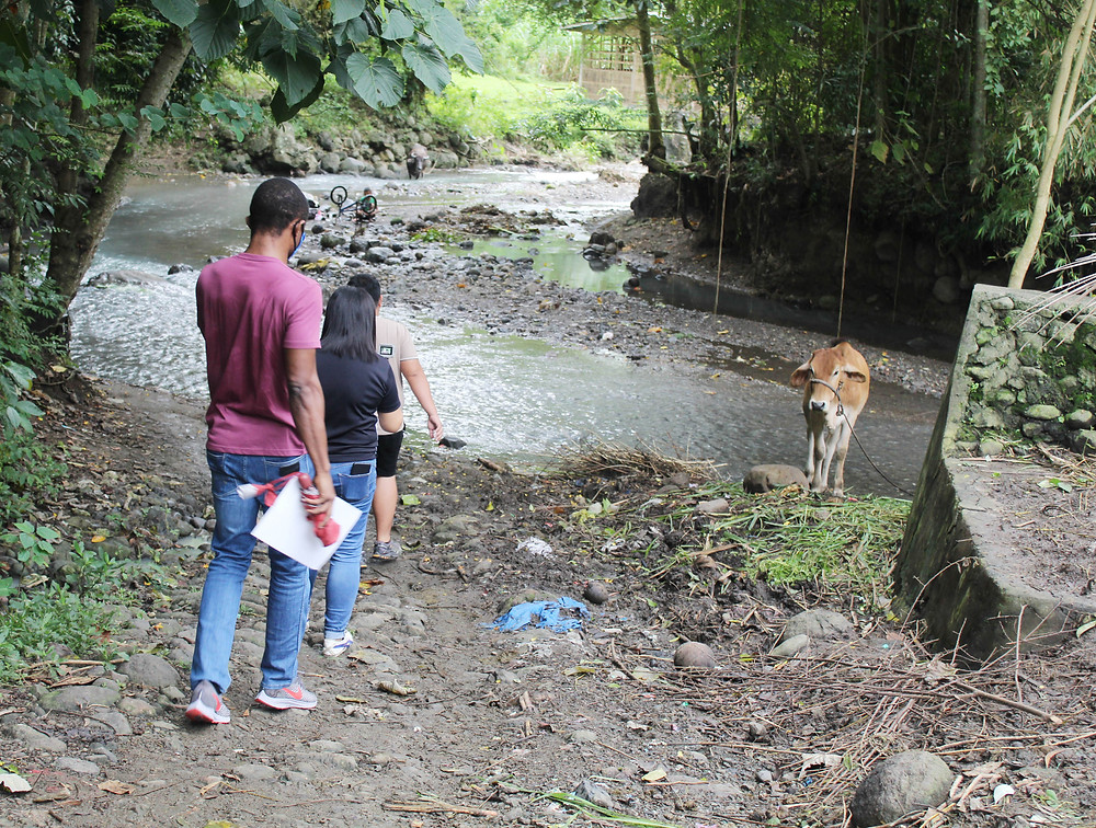 The Long Walk to Ansulag. Rev. Fr. Monday Benjamine Edobor, OAR (leftmost) personally experiences the hike to across a river and the mountains to get to Ansulag Elementary School. With him is Ms. Ma. Nita V. Bolo and Mr. Raian Olvido.