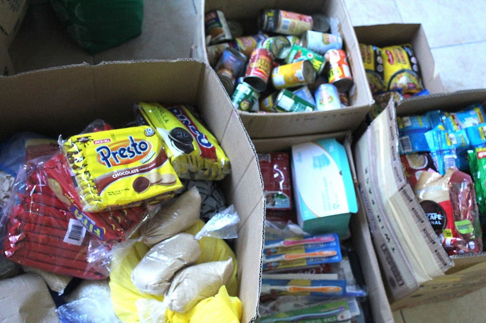 Blessings for all. Boxes of biscuits, canned goods, hygiene products, noodles, milk and coffee powder are packed for the parishioners of San Nicolas de Tolentino Parish whose homes were flooded.