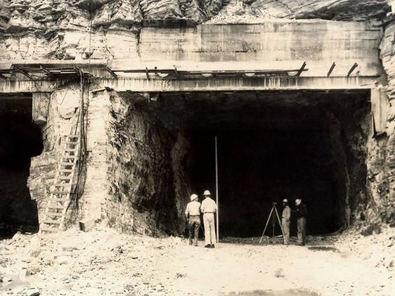 Construção dos túneis de desvio do rio Grande, parte das obras da Usina de Furnas: engenheiros examinam a área externa do túnel.
