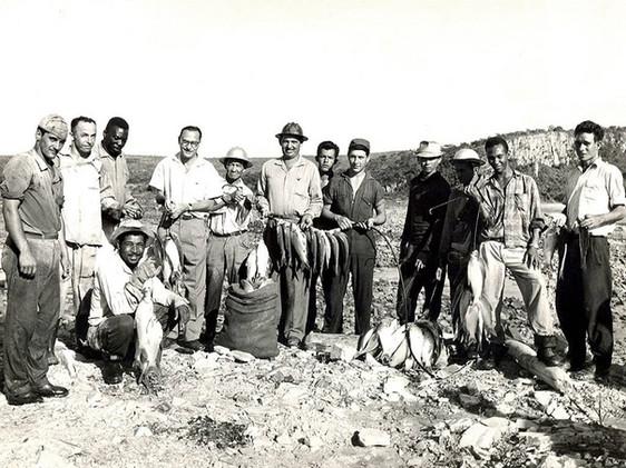 John Cotrim (em pé, o quarto da esq. para dir.) e pescadores no leito do rio Grande após o fechamento dos túneis de desvio.  Janeiro, 1963  J. R. Nonato