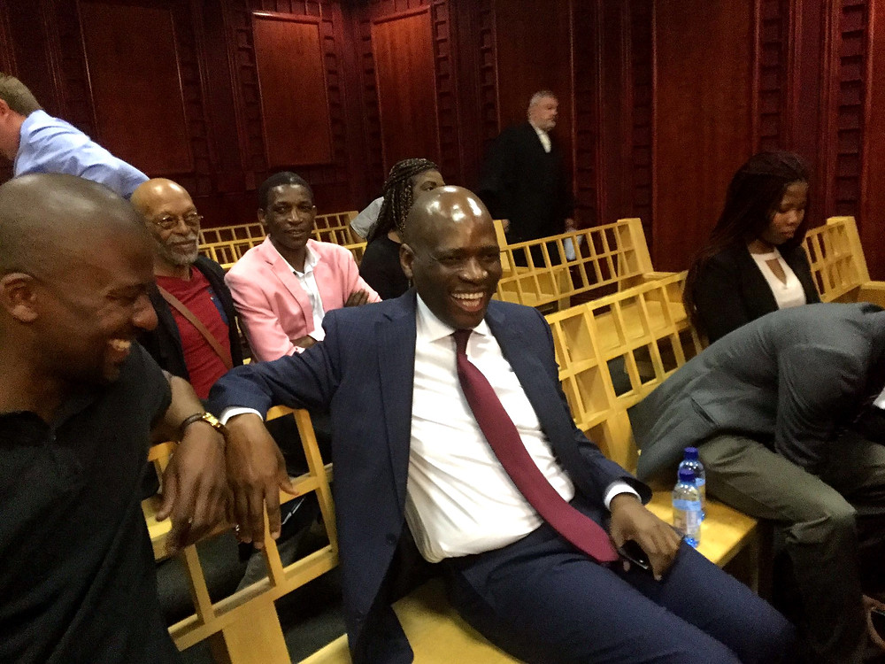 former sabc coo Hlaudi Motsoeneng laughs in the labour court, surrounded by supporters. SABC8
