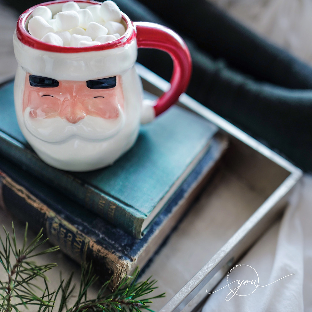 Santa claus mug filled with hot cocoa and mini marshmallows sitting atop two old books, in a wooden tray.