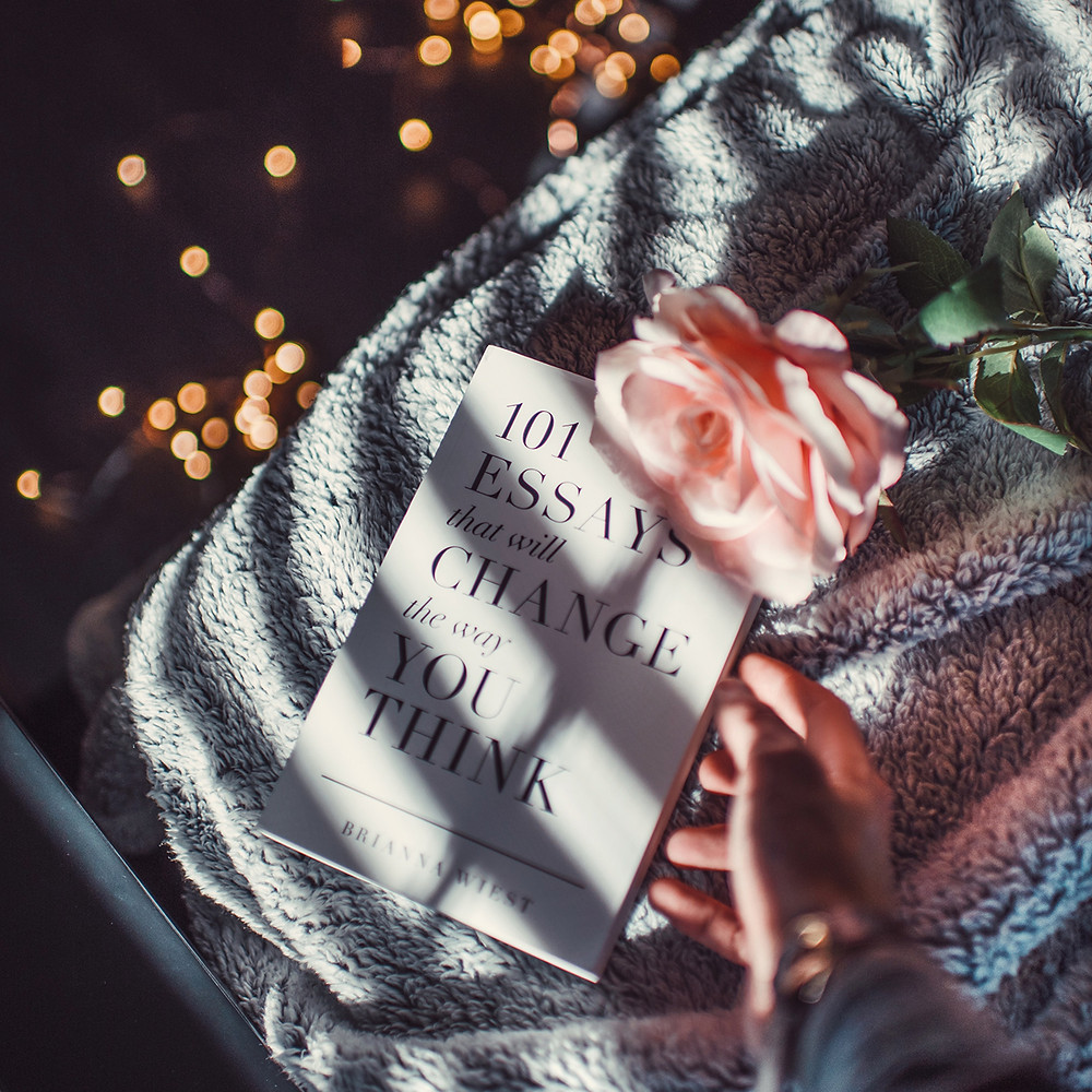 WOman with a cozy blanket, book of essays on change, and a pink rose on her lap, with twinkle lights in the background.