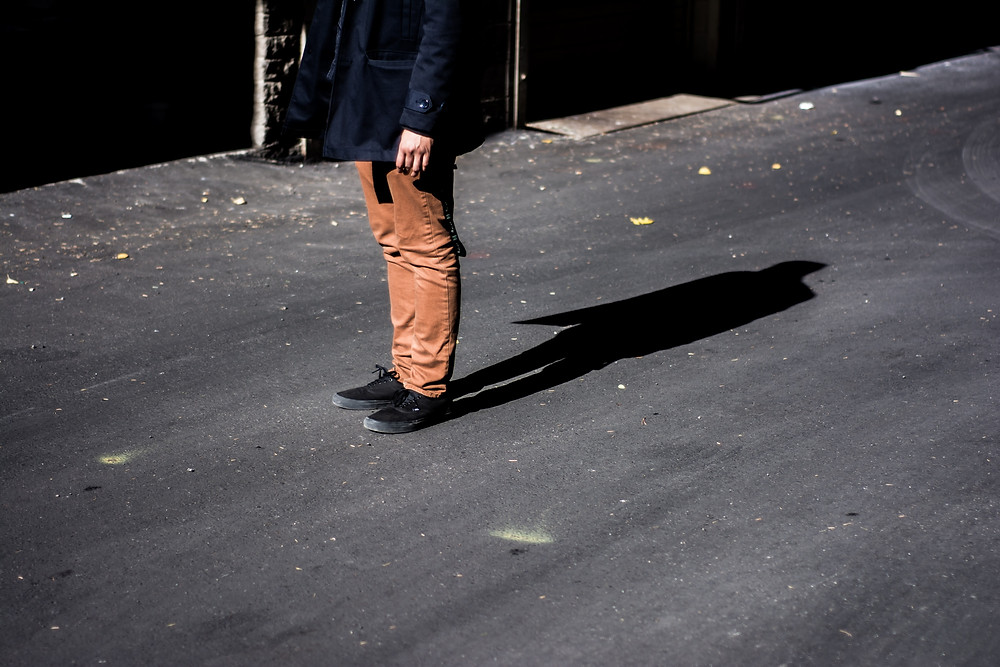 man in brown pants,black shoes and a navy coat standing on asphalt road with long shadow behind him
