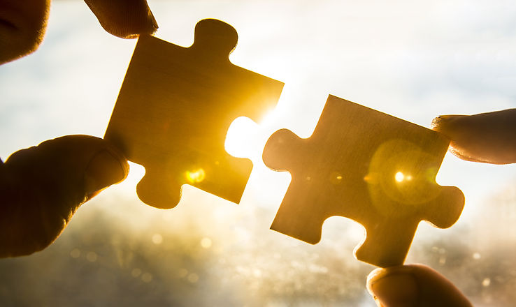 two hands trying to connect couple puzzle piece with sunset background. Jigsaw alone wooden puzzle a