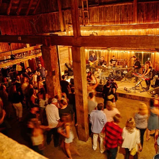 A band plays live music onstage to a crowed bar at the Hayloft Dancehall