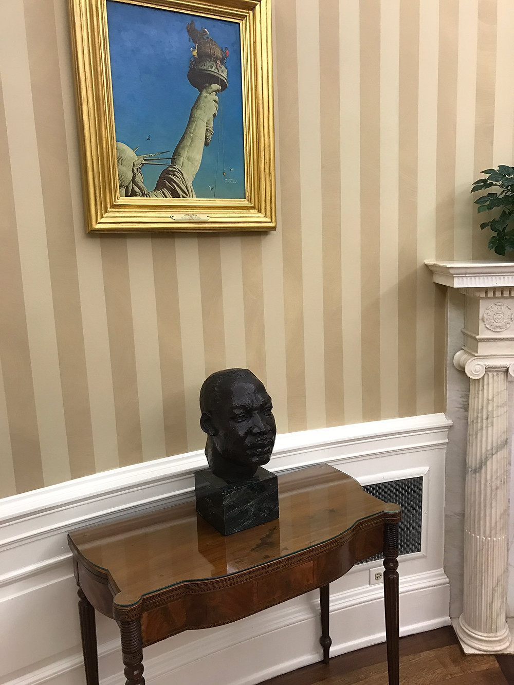 Alston bust of Rev. Martin Luther King Jr. in the Oval Office on 20 January 2017, below Norman Rockwell's painting Working on the Statue of Liberty, Photograph taken by Sean Spicer.