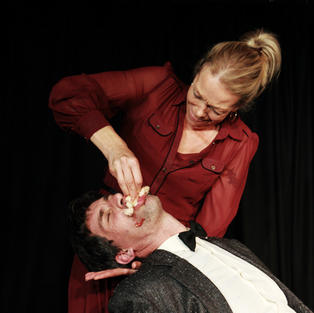 Murdering Peter Oswald on stage with a doughnut