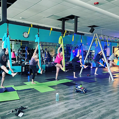 Aerial Yoga class trying new fitness stretch Fitness Inspired Studio