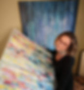 Here is Roxanne Smit holding an abstract painting with another recent one in the background