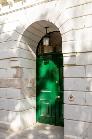 The entrance to the Porthpean House is an arched green door framed with white brick. The many trees on the property create a speckled texture of light dancing on the doorway.  Wanderlost Magazine   Sam MacDonald