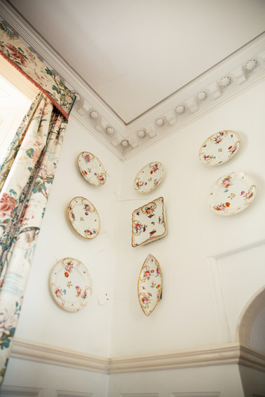 China decorated with delicate flowers hangs in rows on a corner wall next to a window in Porthpean House.  Wanderlost Magazine | Sam MacDonald