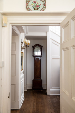 An open door leads into a hallway with a grandfather clock in Porthpean House.  Wanderlost Magazine | Sam MacDonald