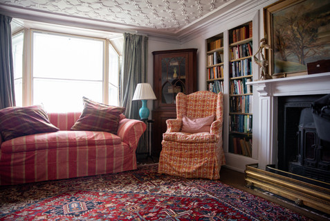 A plush couch and rocking chair stand in a corner in Porthpean House. The room is decorated with an oriental rug, a fireplace, and book shelves.  Wanderlost Magazine   Mary Kathryn Carpenter