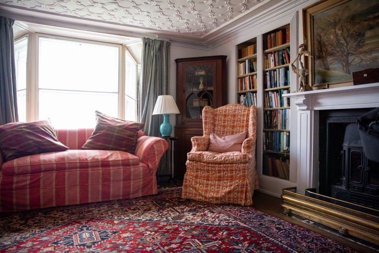 A plush couch and rocking chair stand in a corner in Porthpean House. The room is decorated with an oriental rug, a fireplace, and book shelves.  Wanderlost Magazine | Mary Kathryn Carpenter